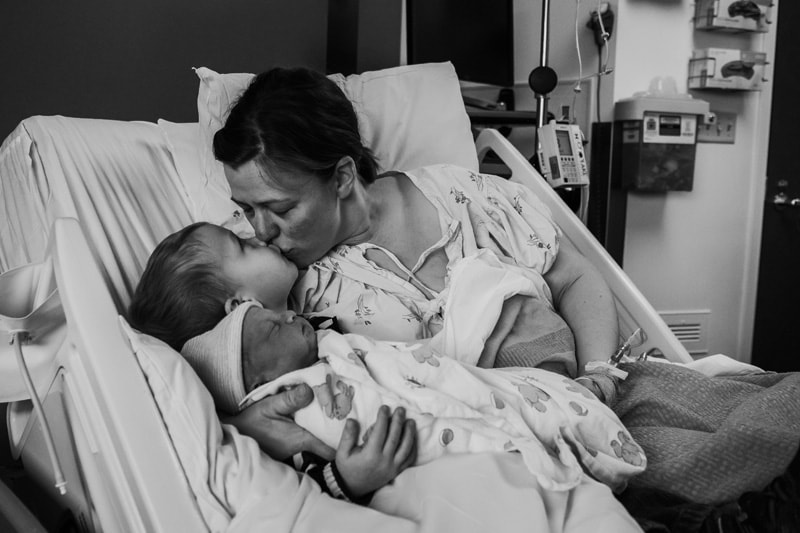 Seattle Birth Photography, mother leaning down to kiss her older child