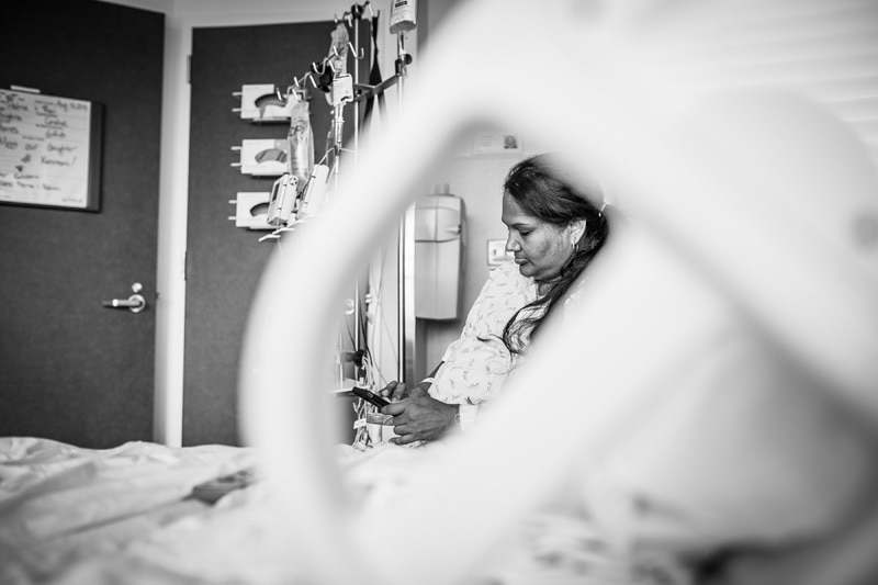 Seattle Birth Photography, looking at laboring mother through the arm of the hospital bed