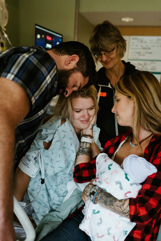 Denver Birth Photographer, new mama looking at her baby in another woman's arms