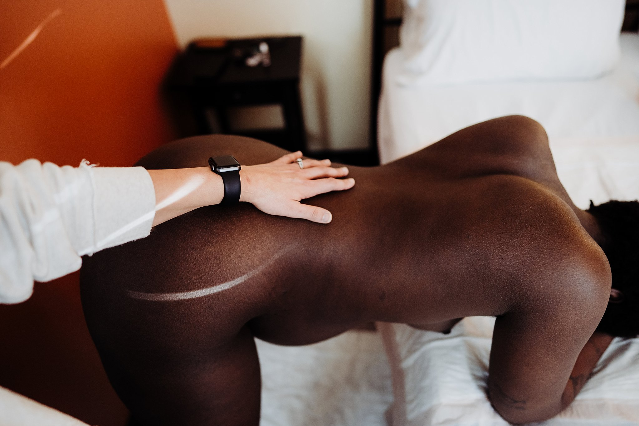 birthing person is leaning over the bed using her elbows for support. Her partner has her hand gently placed on the small of her back, a thin light strip from the window forming the shape around her hip